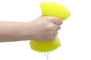 Hand squeezing drip out of large yellow sponge on white background, isolated
